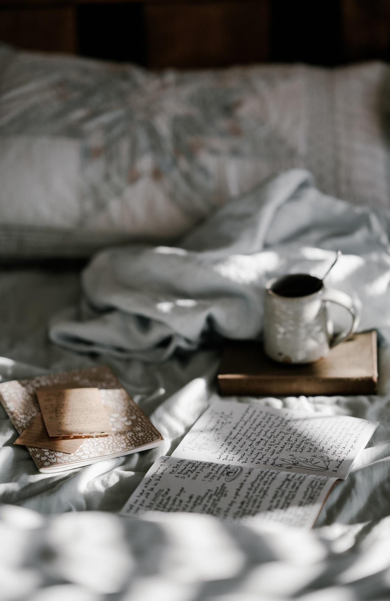 Foto van een slaapkamer in ochtendlicht met allerlei spullen op het bed.