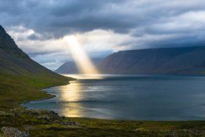 foto lichtstraal uit wolk boven baai via Unsplash, Davide Cantelli