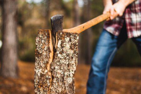 Man hakt houtblok doormmidden met een bijl