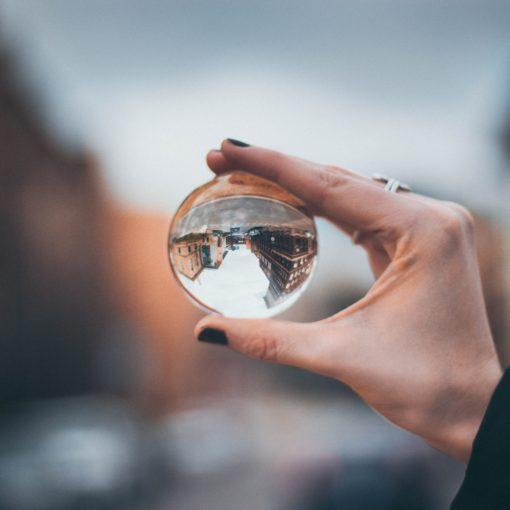 Vrouwenhand houdt glazen bol vast waarin huizen op de kop weerspiegeld worden. Foto via Unspash Anika Huizinga
