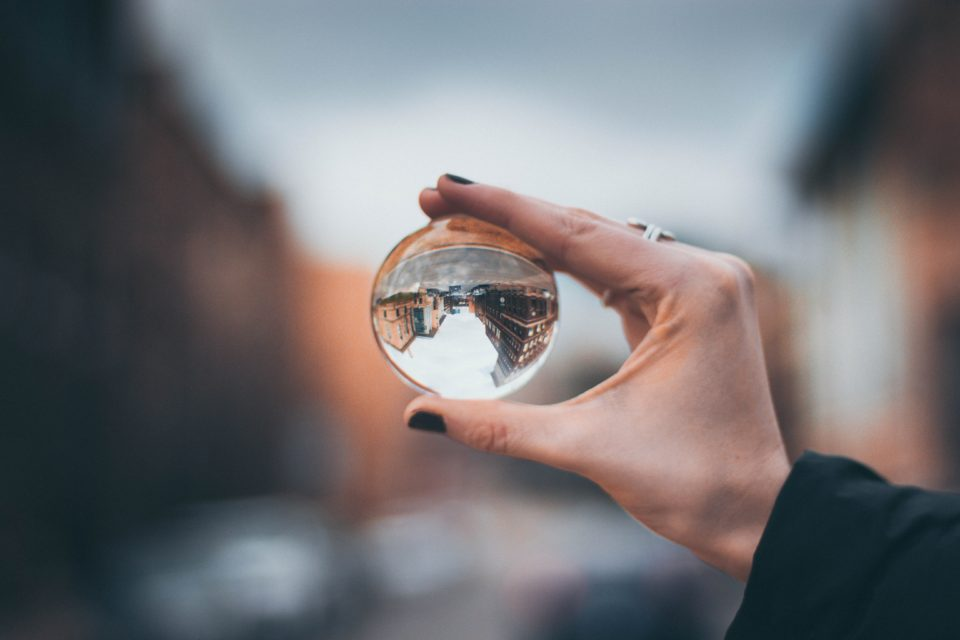 Vrouwenhand met glazen bol waarin de wereld op zijn kop weerspiegeld wordt, vage achtergrond. Foto via Unsplash van Anika Huizinga