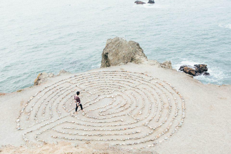 Persoon loopt in labyrinth van stenen op een strand. Photo by Ashley Batz on Unsplash