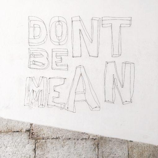 handlettered tekst: Don't be mean; foto door Ashley Whitlatch via Unsplash
