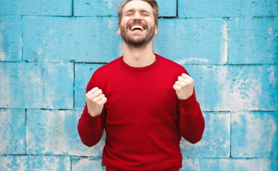 man in rode trui voor blauwe muur balt zijn vuisten van geluk. Via Unsplash, Bruce Mars