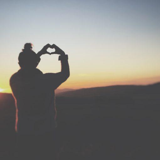 Silhouet van iemand die met zijn handen een hartje vormt; foto van Cerys Lowe via Unsplash