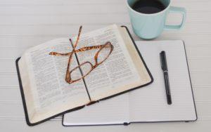 Leesbril op opengeslagen boek op leeg notitieboek met pen ernaast. Photo by Debby Hudson on Unsplash