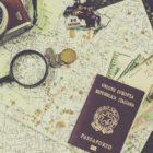 Samengesteld beeld met een landkaart, fototoestel, vergrootglas, munten, briefgeld en een paspoort. Photo by Francesca Tirico on Unsplash