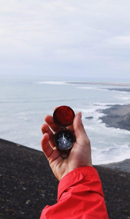 mannenhand houdt open kompas vast bovenaan een klif bij de zee