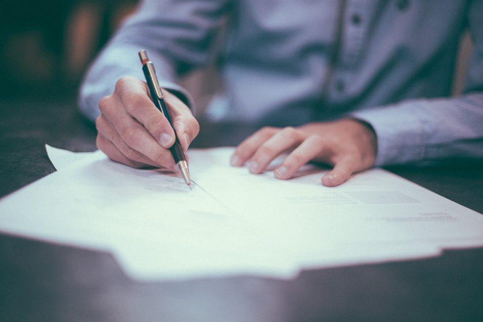 Man schrijft met pen op een papier, ondertekent een contract; foto van Helloquence op Unsplash
