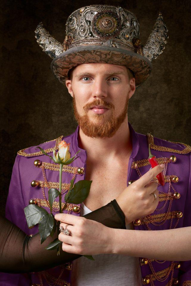 Man in theatrale kleding kan kiezen tussen 2 vrouwen: 1 biedt een roos aan, de ander een rode peper