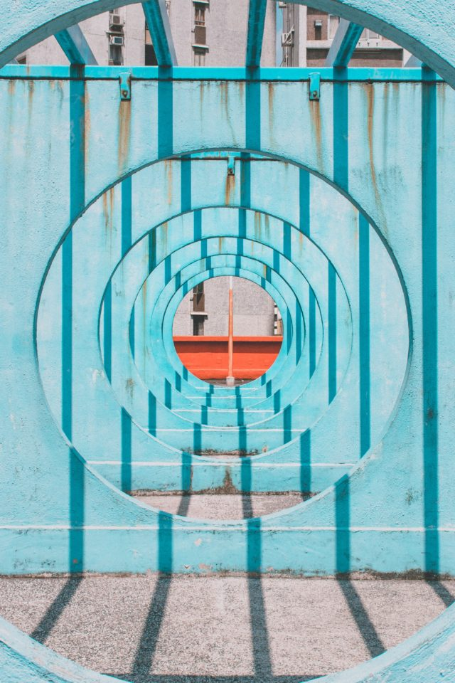 Blauwe ronde tunnel met zicht op de opening, daar staat een mast? in het midden. Via Unsplash, Joel Fulgencio