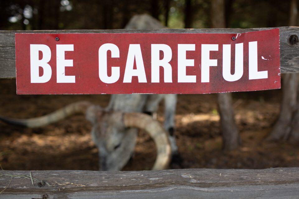 Rood bordje op hek met tekst: Be careful (wees voorzichtig)