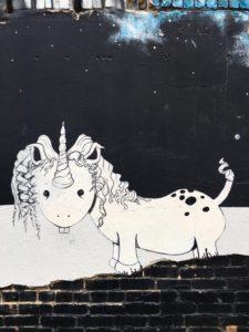 Zwart-witte muurschildering van een eenhoorn. Photo by Karen Powers on Unsplash