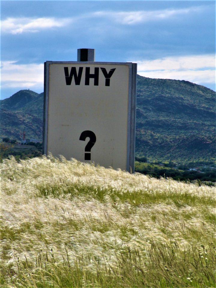 Bord met de tekst Why? bovenop een heuvel of berg