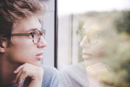 man kijkt naar reflectie in raam