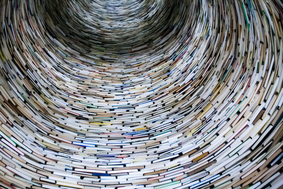 laagperspectief foto binnenin een toren van boeken; foto van Lysander Yuen op Unsplash