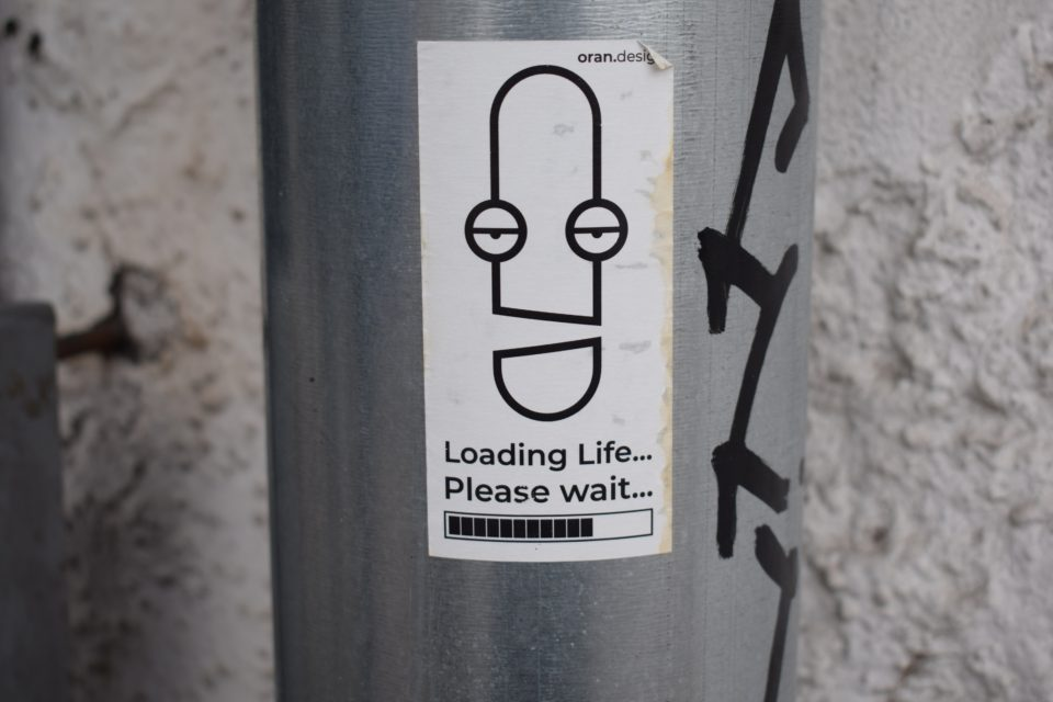 Sticker op een metalen paal met de tekst: Loading life...Please wait; foto van Marija Zaric op Unsplash