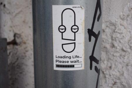 Sticker op een metalen paal met de tekst: Loading life...Please wait; foto van Marija Zaric op Unsplash