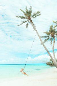 Vrouw schommelt onder een kokosboom op een tropisch strand. Photo by Marvin Meyer on Unsplash