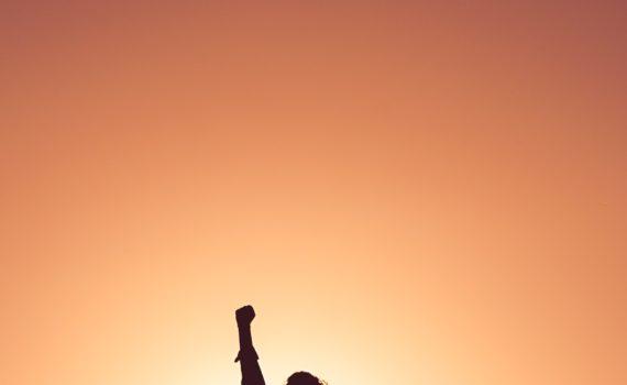 Silhouet van persoon met gebalde vuist in de lucht tegen oranje lucht; foto van Miguel Bruna via Unsplash