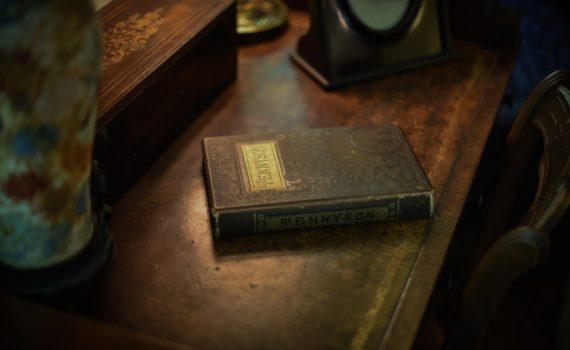 Foto van oud bruin ingebonden boek op een ouderwets houten bureau