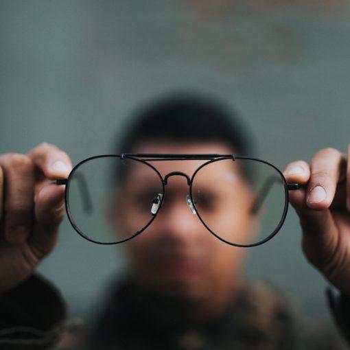 Man, onscherp, houdt grote bril vast op de voorgrond. Foto via Unsplash, Nathan Dumlao