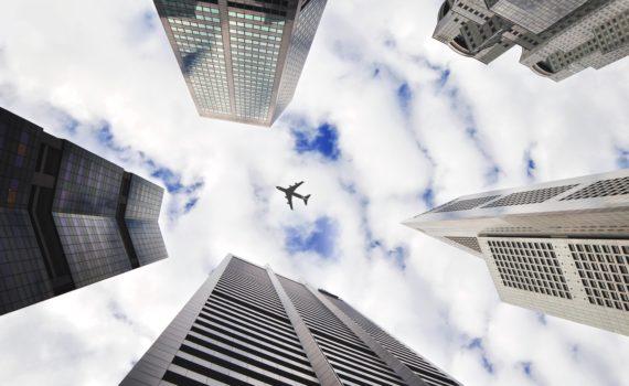 laagperspectief foto van 5 wolkenkrabbers met in het midden een vliegtuig tegen witte wolken. foto via Unsplash,