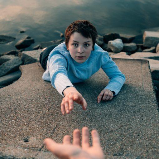 Vrouw (klimt tegen wand boven water) steekt haar hand uit naar een uitgestoken hand van iemand anders; Photo by Noah Buscher on Unsplash