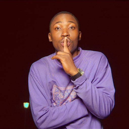 Man in paarse trui maakt het 'stilte'gebaar met een vinger op zijn lippen; Photo by Ocean Biggshott on Unsplash