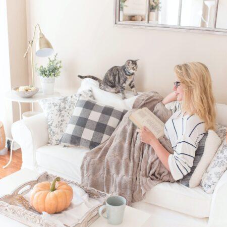 Vrouw zit comfortabel te lezen in hoek van bank, dekentje, kat