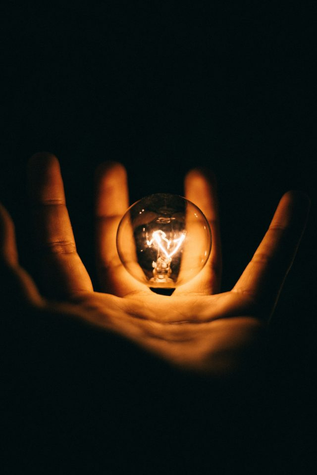 Brandende gloeilamp in hand. Photo by Rohan Makhecha on Unsplash
