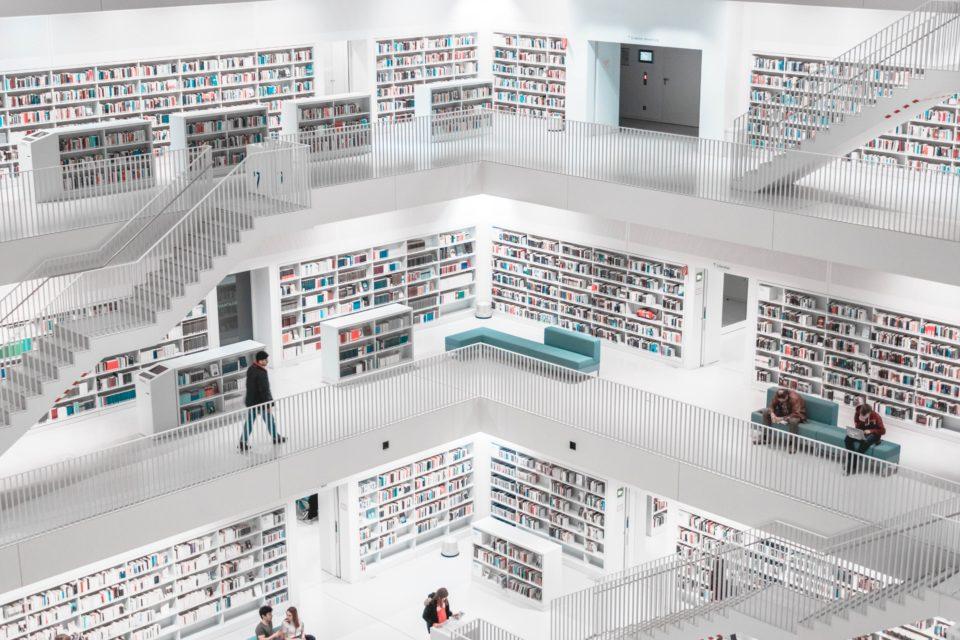 Mensen lopen en zitten in een moderne witte bibliotheek, trappenhuis; foto van Sara Kurfeß on Unsplash