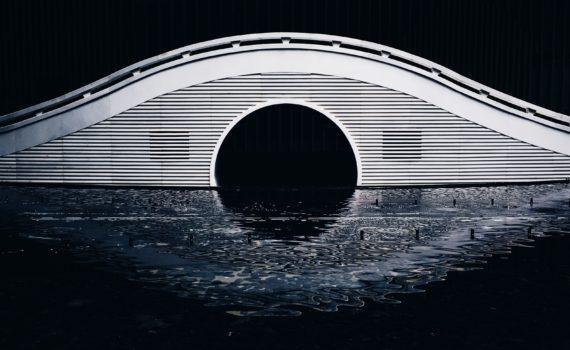 Witte brug met sierlijke boogvorm en weerspiegeling in het water; Photo by Sean Kowal on Unsplash