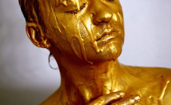 Persoon met gesloten ogen, bedekt met goudkleurige vloeistof; Photo by Sharon McCutcheon on Unsplash