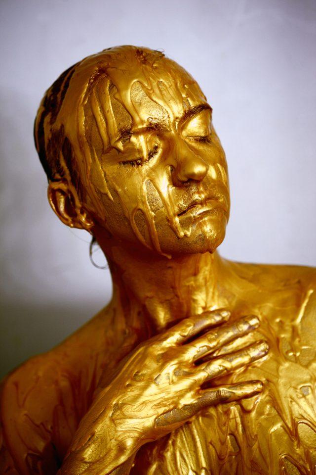 Hoofd van iemand met gesloten ogen die is bedekt met een goudkleurige vloeistof
