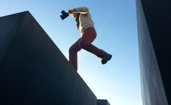 Man springt over een kloof tussen twee gebouwen, laagperspectief; foto van Sonja Guina via Unsplash