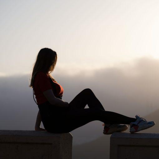 foto verbeeldt zowel twijfel als zekerheid: vrouw zit met billen op randje, voeten (na gat) op ander randje
