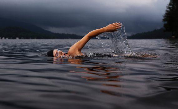 Man met zwembril en -muts zwemt in een meer tussen heuvels; Photo by Todd Quackenbush on Unsplash