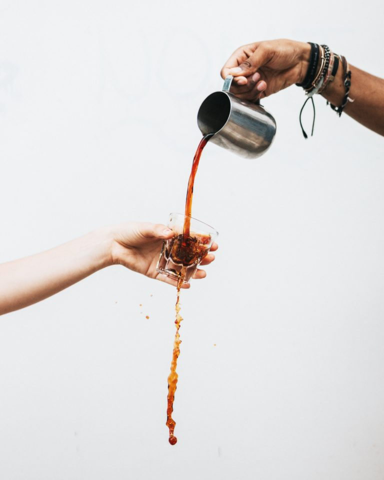 Iemand schenkt koffie door een glas heen; Photo by Tyler Nix on Unsplash