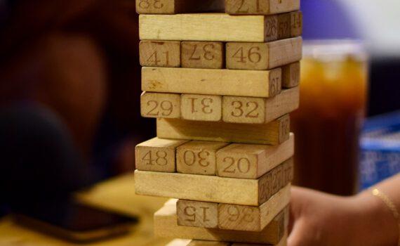Foto van het spel Jenga. Wie trekt het staafje eruit waardoor de toren omvalt?