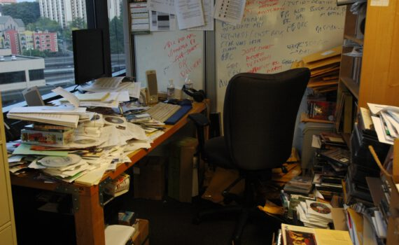 Heel rommelige kamer met vol bureau overal stapels